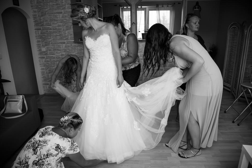 Družičky pomáhají nevěstě obléct svatební šaty