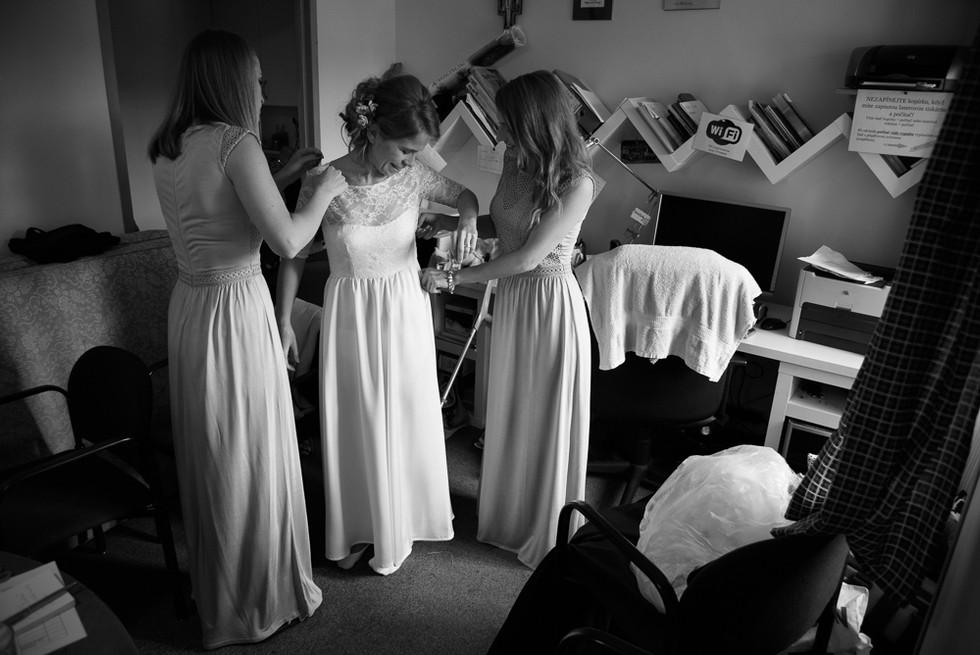 Družičky pomáhají nevěstě do svatebních šatů na skautské základně v Hostinné