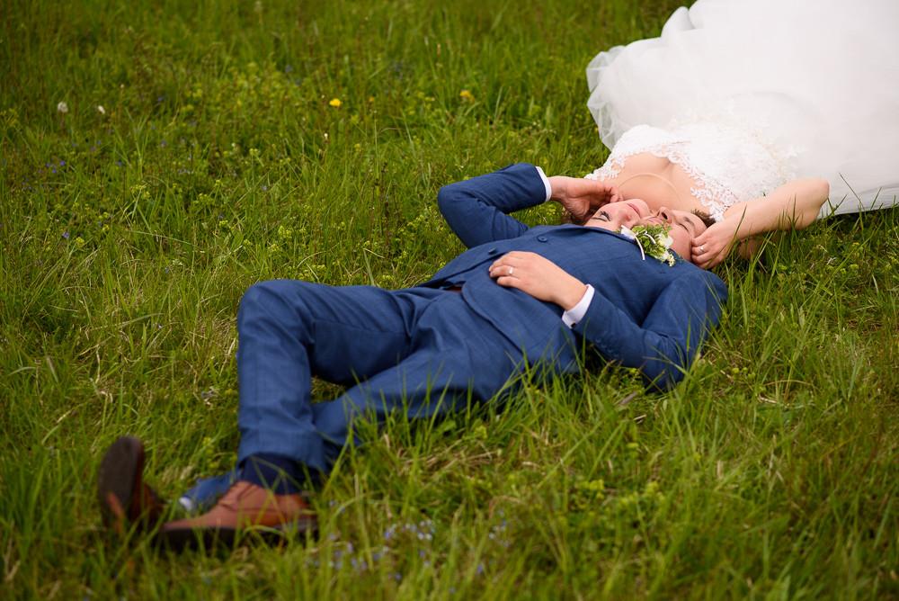 Ženich s nevěstou leží na trávě na louce u Průchodnic.