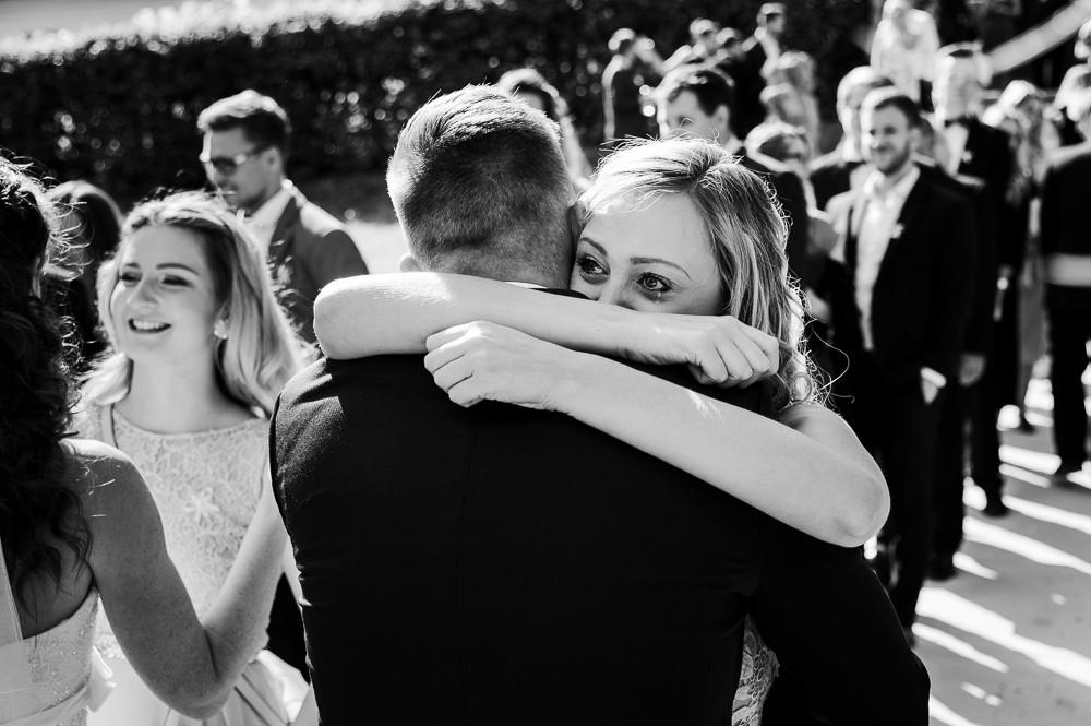 Dojatá družička objímá ženicha po obřadu v Náměšti na Hané.