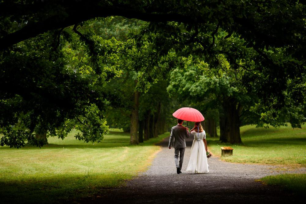 Novomanželé jdou za deště s červeným deštníkem alejí stromů v zámeckém parku v Čechách pod Kosířem.