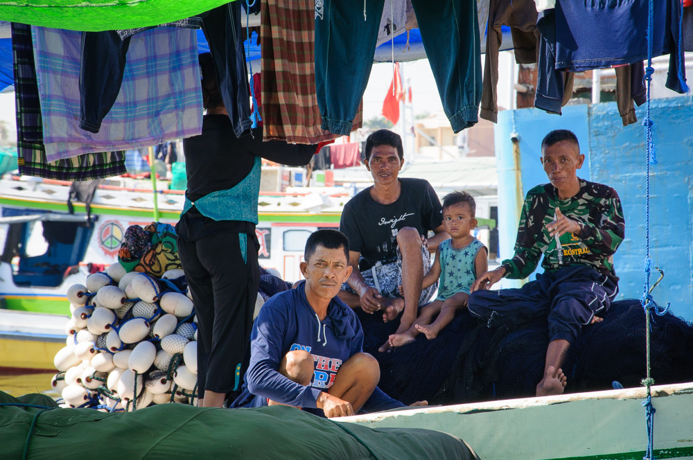 Portrait of a family on a boat in Port Paotere in Makassar, South Sulawesi, Indonesia.