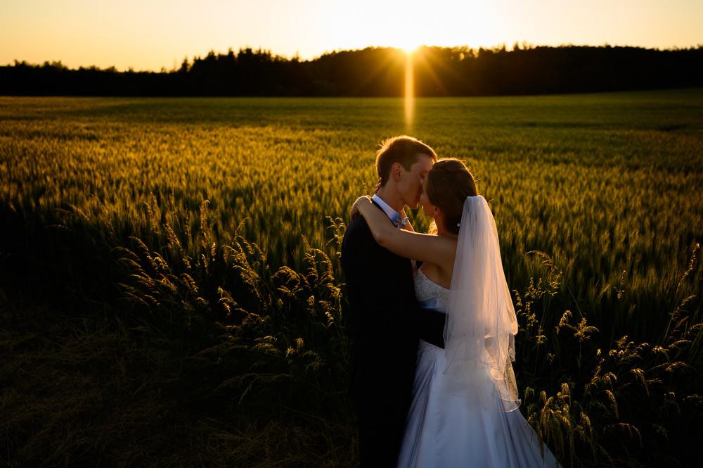 Polibek novomanželů při západu slunce.