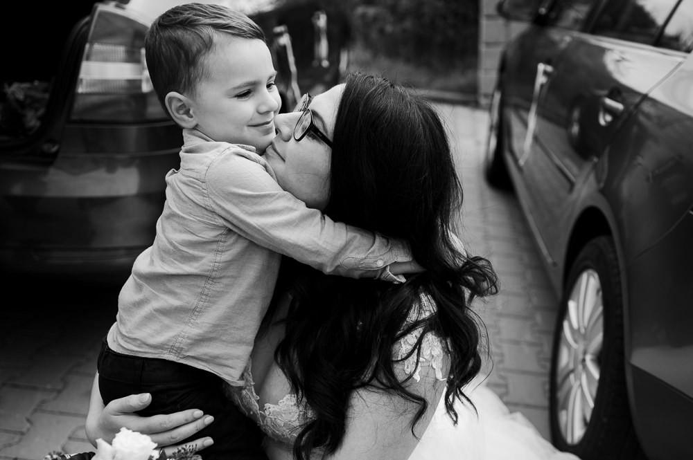 Syn objímá mámu nevěstu po příjezdu na hostinu.