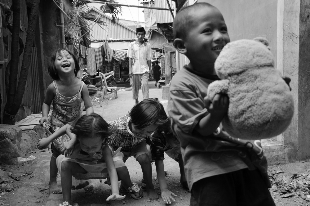 The power of being present. Children enjoy themselves while following visitors in the surrounding streets of Port Paotere in Makassar, South Sulawesi, Indonesia.