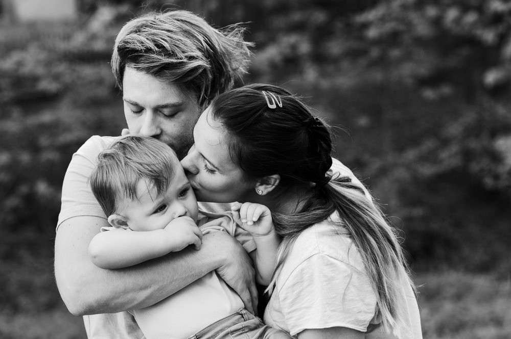 Rodiče objímají a pusinkují své dítě při intimním momentu při profesionálním focení.