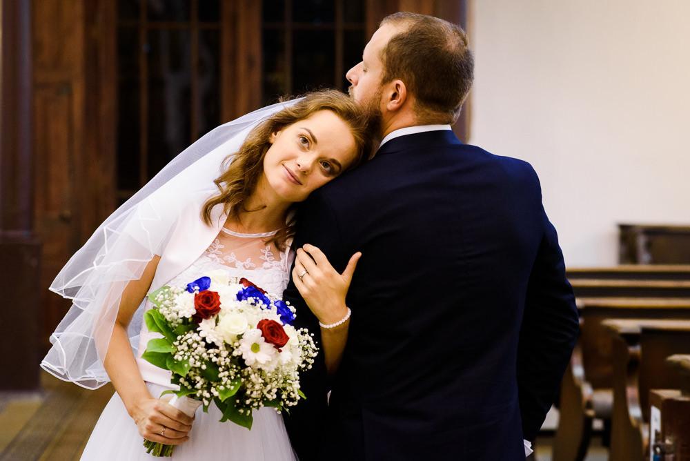 Nevěsta s červenobílomodrou svatební kyticí objímá ženicha a leží na jeho rameni v olomouckém kapucínském klášteře.