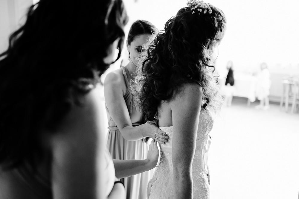 Družičky zapínají nevěstě svatební šaty.