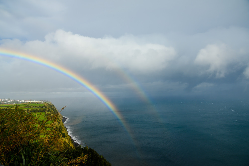 Double rainbow above the ocean shows unpredictable weather at Sao Miguel, Azores.