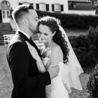 Ženich objímá nevěstu poté, cosi řekli ano při venkovním obřadu na zámku v Náměšti na Hané.