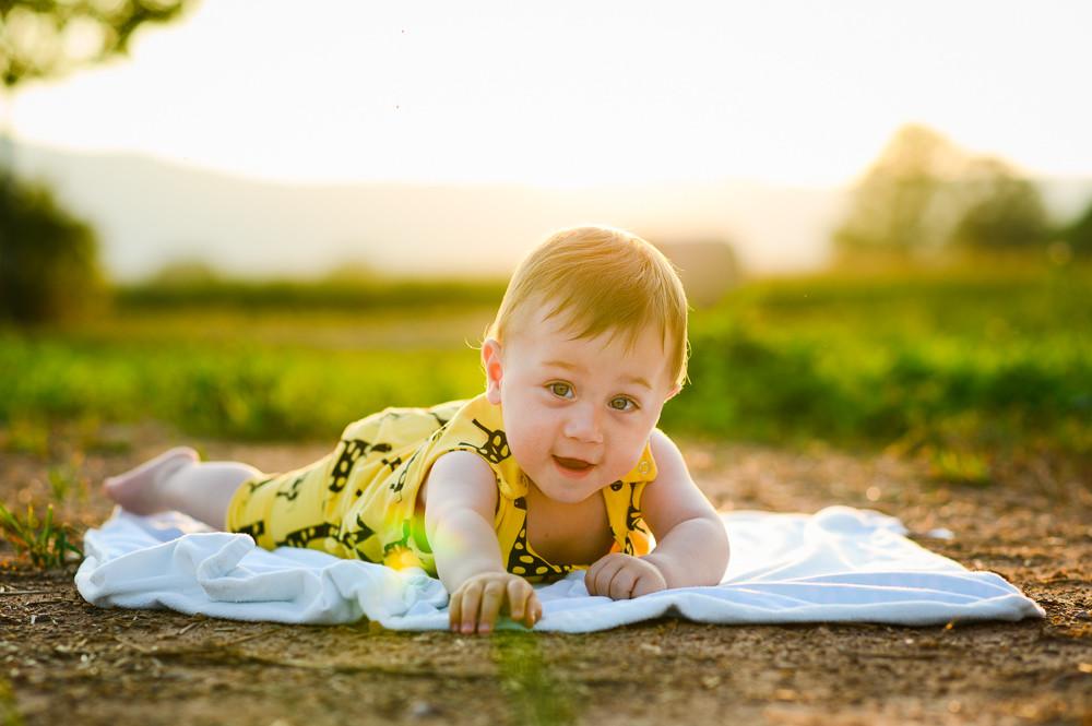 Portrét dítěte na dece při západu slunce.
