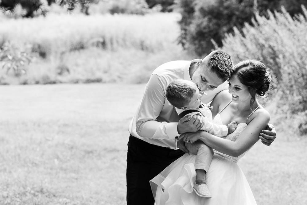 Rodinný portrét rodičů novomanželů a jejich syna na svatbě.