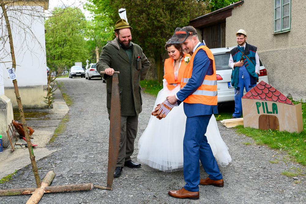 Novomanželé v oranžových vestách se připravují na pokácení stromů v rámci zalikování.
