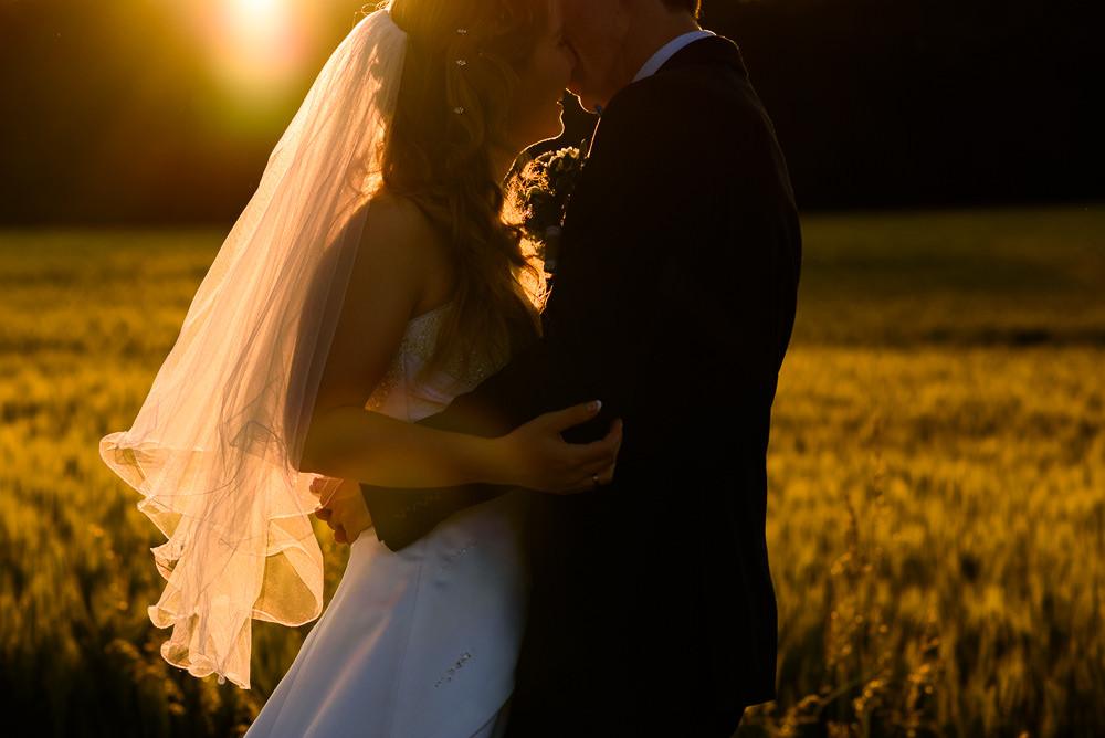 Ženich s nevěstou v poli při portrétním focení při západu slunce.