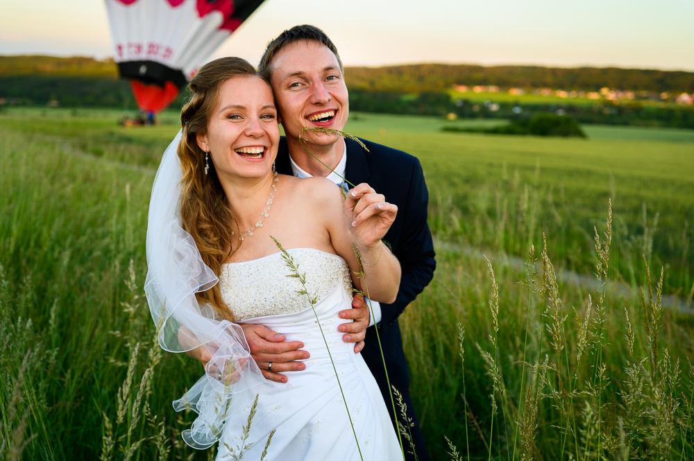 Novomanželé v trávě pózují před balónem.