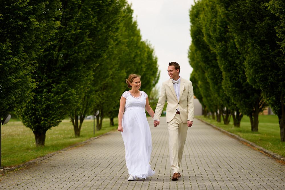 Novomanželé v bílém jdou alejí stromů v areálu Prachárna Park Hotel Olomouc.