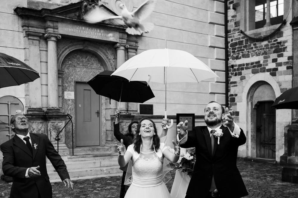Novomanželé vypouštějí holubice před katedrálou.