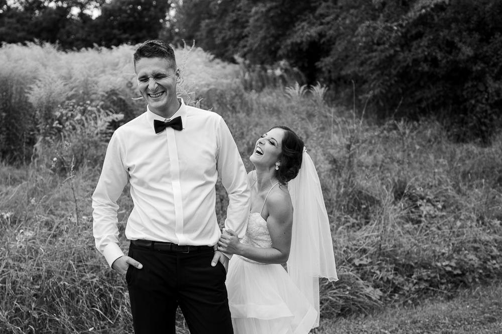 Nevěsta lechtá ženicha trávou při focení.