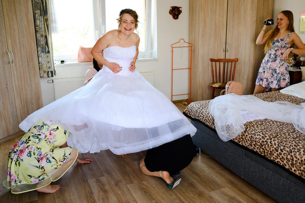 Oblékání šatů nevěsty při ranních přípravách.