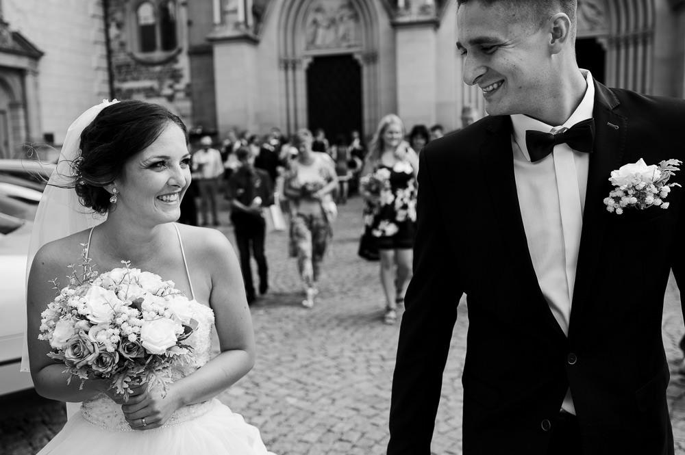 Novomanželé vyšli ven z katedráli a usmívají se na sebe.