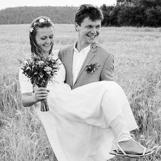 Ženich nese nevěstu při svatebním focení v obilném poli.