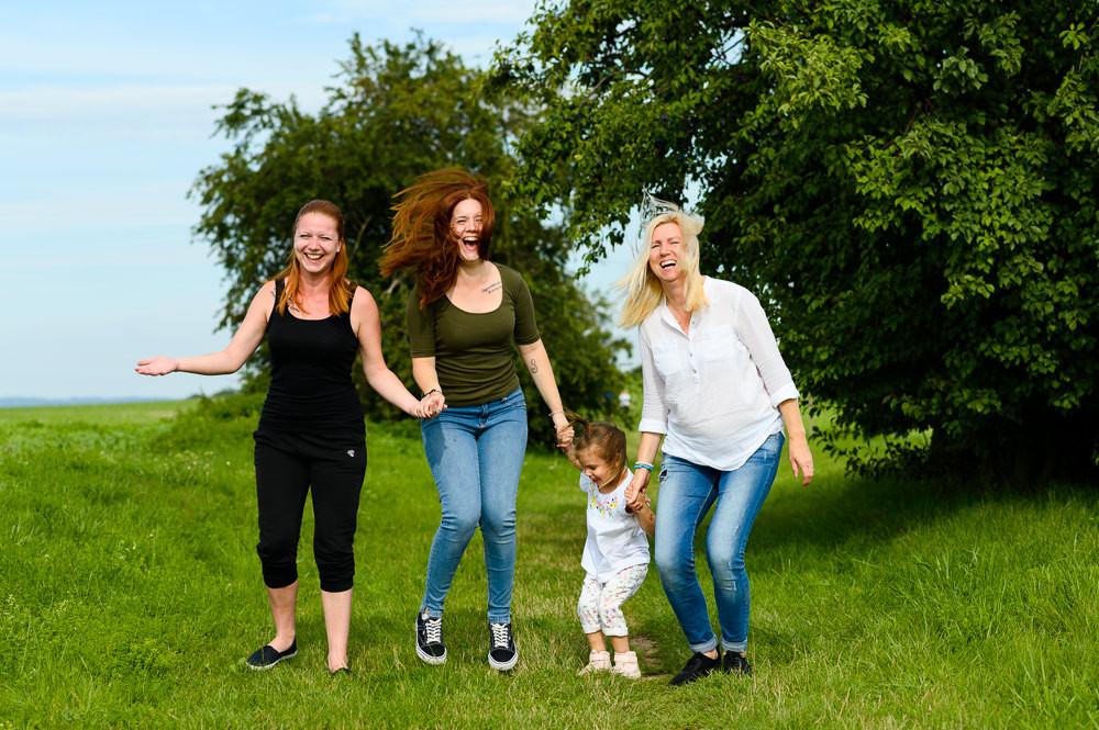 Rodinka skáče venku na trávě při zábavném focení v exteriéru.