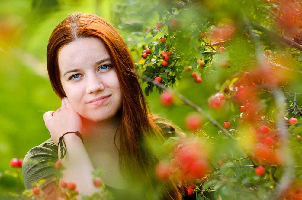Letní portrét mladé dívky venku se šípkovým keřem.