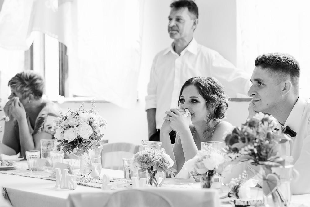 Nevěsta je dojatá při prohlížení prezentací s fotografiemi na svatbě.
