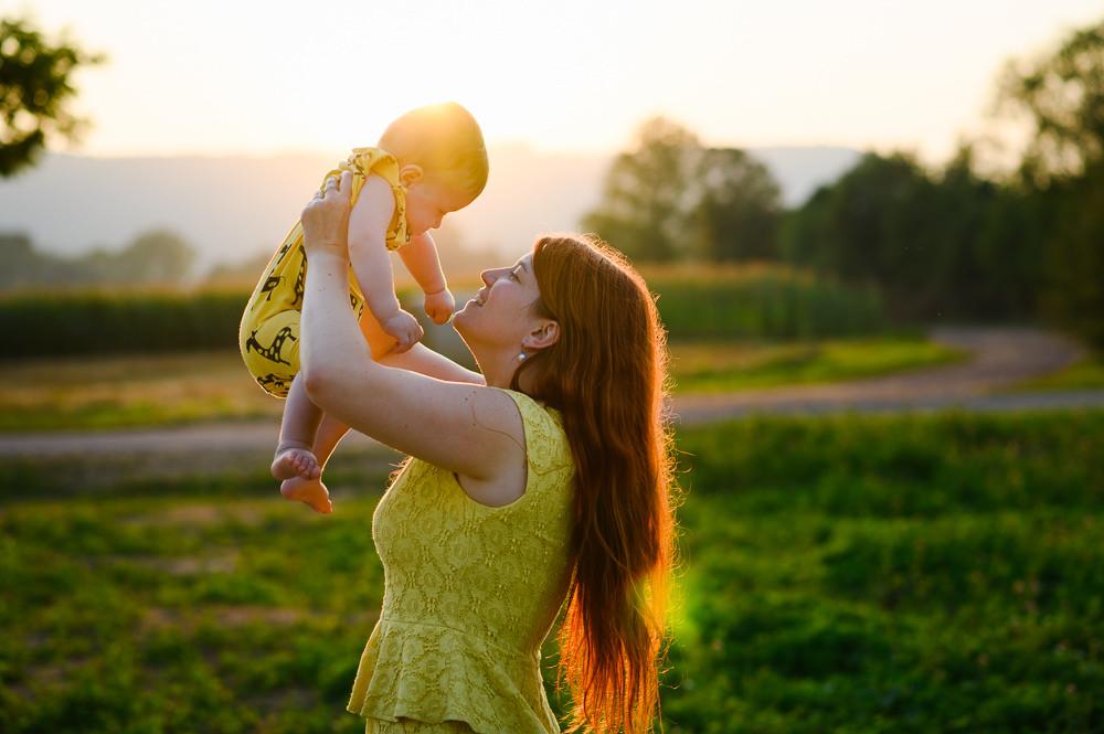 Máma drží syna nad hlavou při portrétním focení za západu slunce.