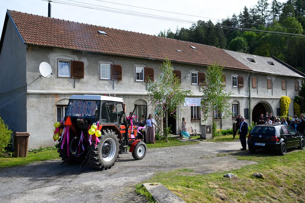 """Ženich přijíždí vyprosit si nevěstu na zdobeném traktoru s transparentem """"zatím svobodný""""."""