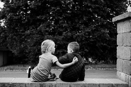 Svatební momentka: děti sedí na zídce na svatbě jejich rodičů.
