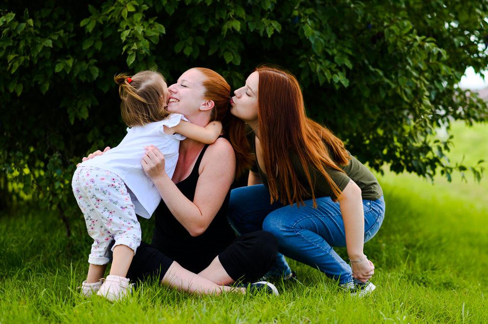 Rodinné focení se sestřenkami, sesterská láska v plném proudu projevená pusinkováním s tříletou sestřičkou.
