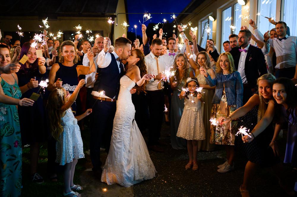 Novomanželé při polibku obklopeni přáteli a rodinou s prskavky při večerním focení v kulturním domě Náměšť na Hané.