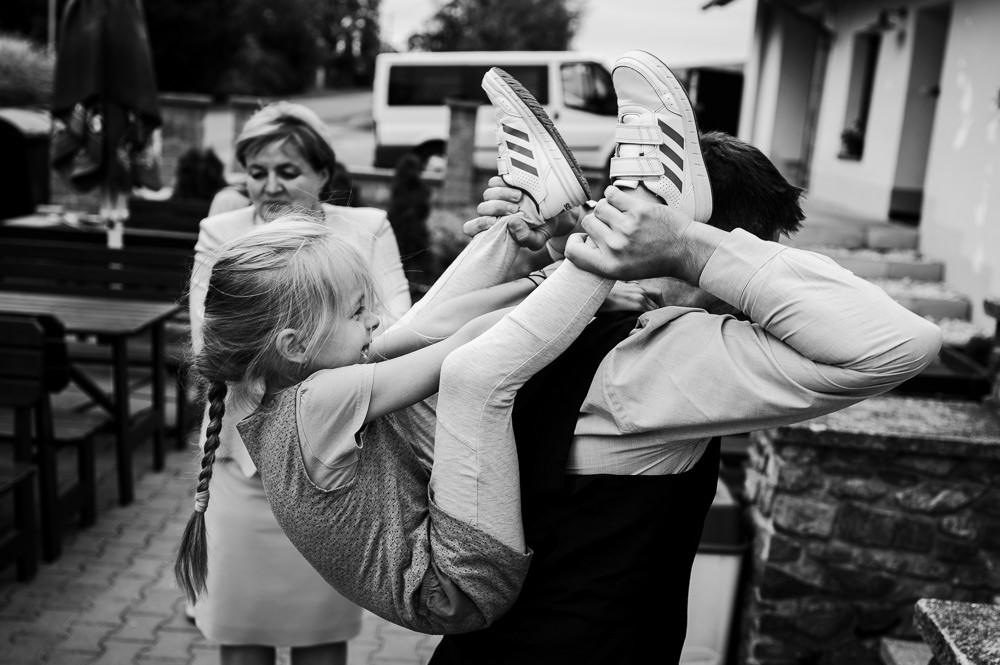 Holčička družička si hraje se svým tátou na svatbě.
