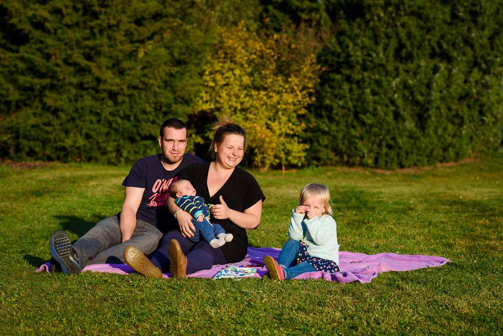 Rodina s malými dětmi při focení na dece na trávě v olomouckém rozáriu.
