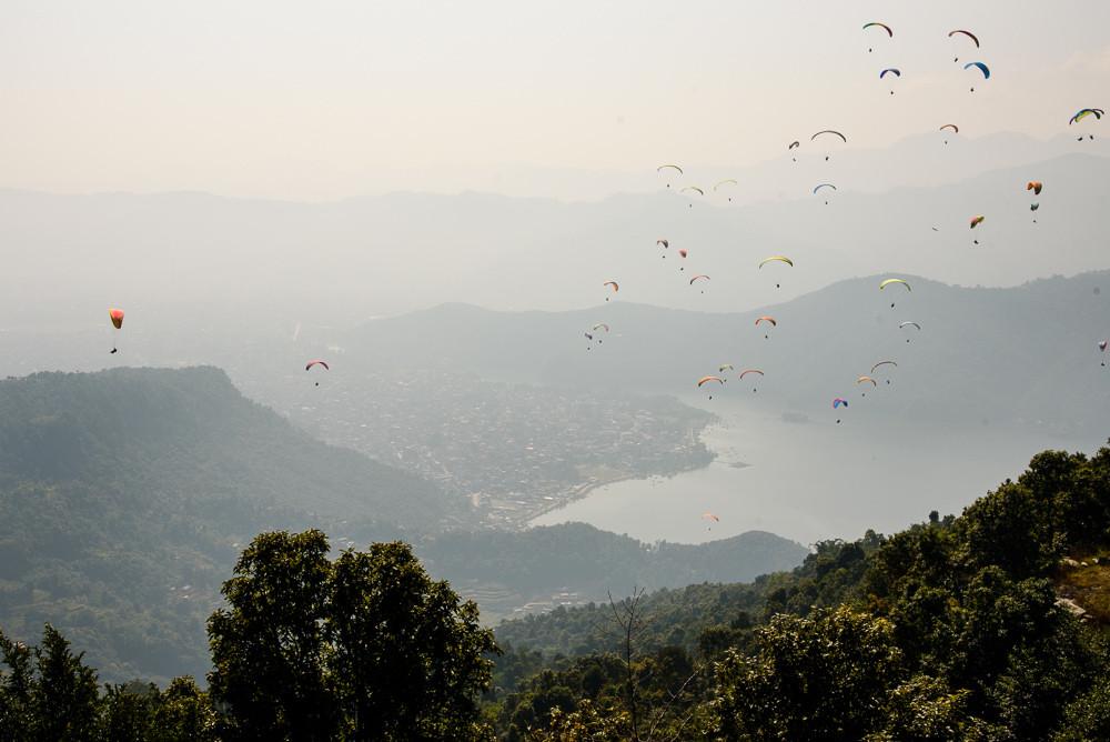 Skok z kopce Sarangkot padákem, paragliding v nepálské Pokhaře nad jezerem Phewa.