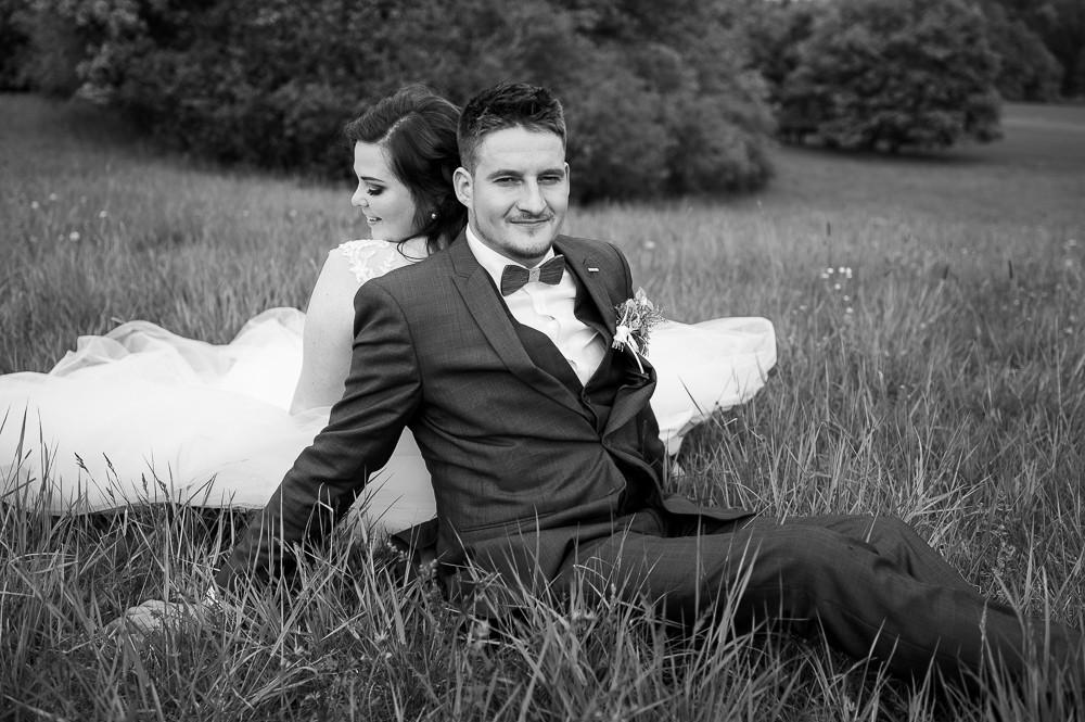 Černobílý portrét novomanželů venku na louce.