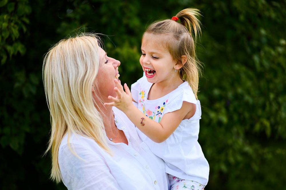 Máma s tříletou dcerkou se smějí při venkovním focení.