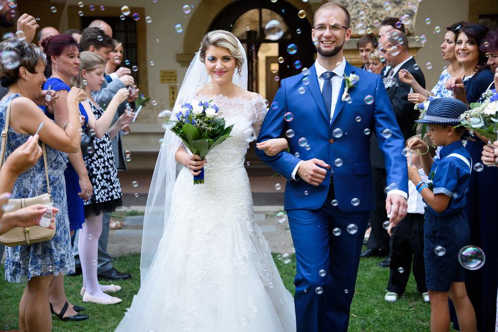 Novomanželé prochází svatebním špalírem bublinkami z bublifuků