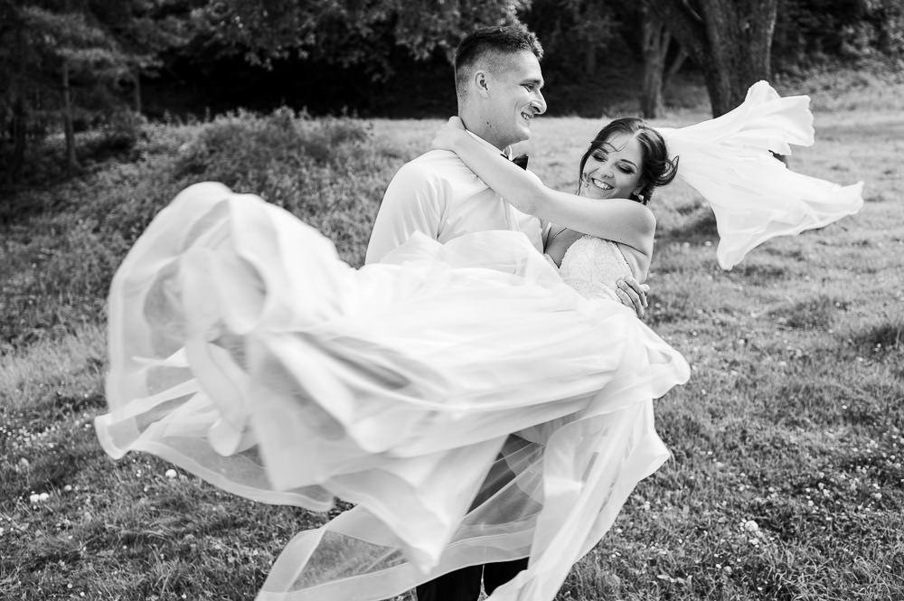 Ženich roztáčí nevěstu při zkoušce prvního tance při svatebním focení novomanželů.