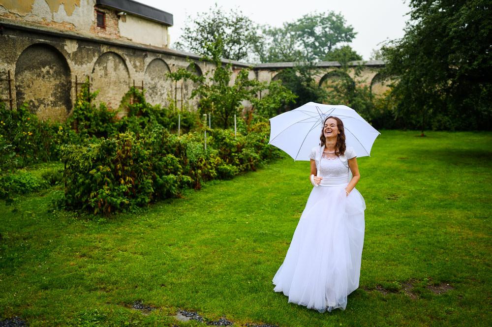 Nevěsta se směje při venkovním portrétním focení ve vinici.
