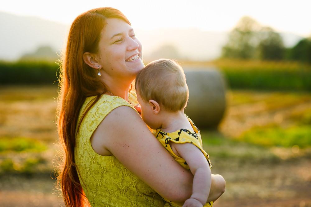 Máma se směje a objímá svého syna při portrétním focení venku.