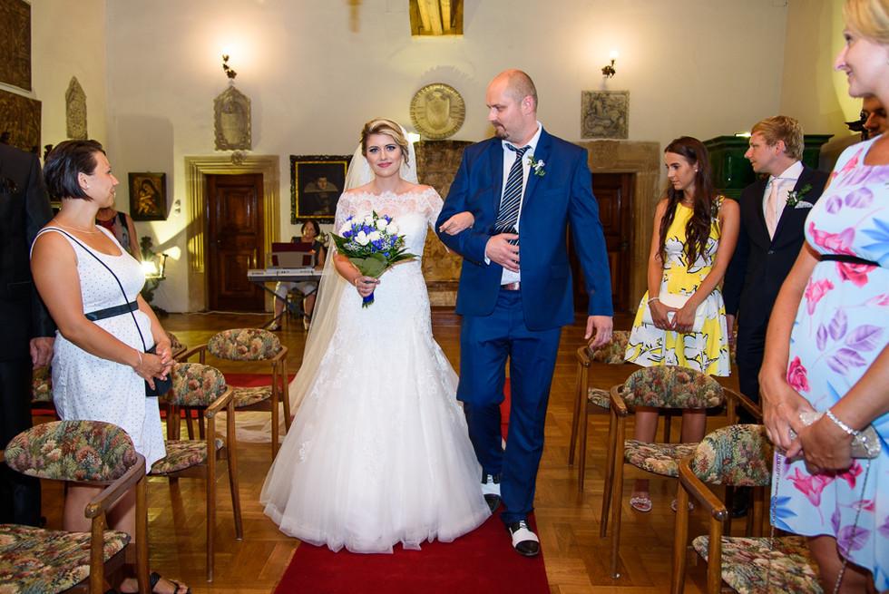 Otec vede nevěstu při obřadu v rytířském sálu na hradě Šternberk