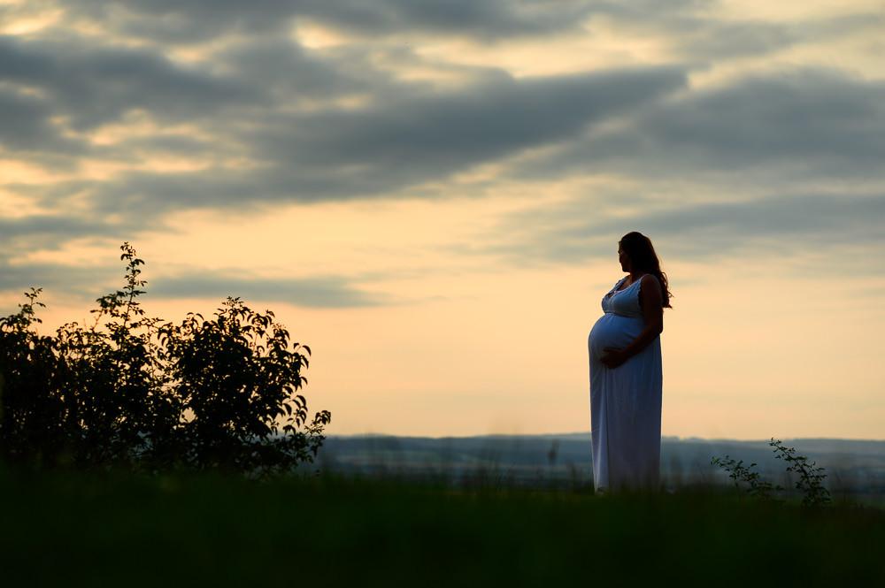 Nastávající maminka se dívá do dáli při těhotenském focení za západu slunce.