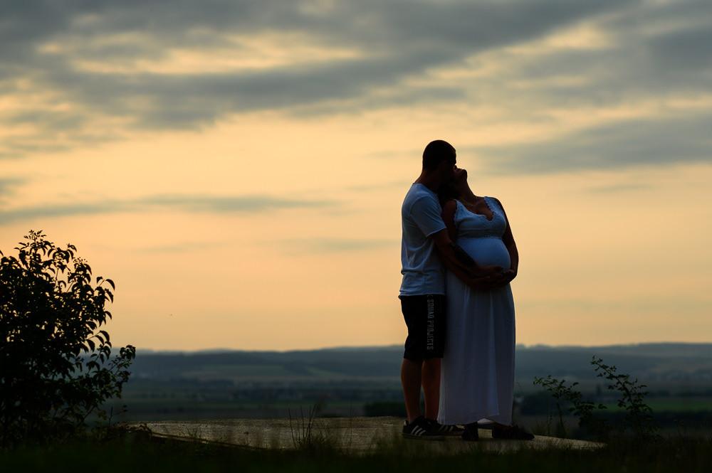 Těhotenské focení mladého páru za západu slunce.