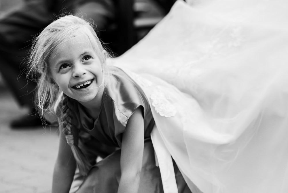 Dítě vykukuje ze svatebních šatů, ze kterých se stala schovka.