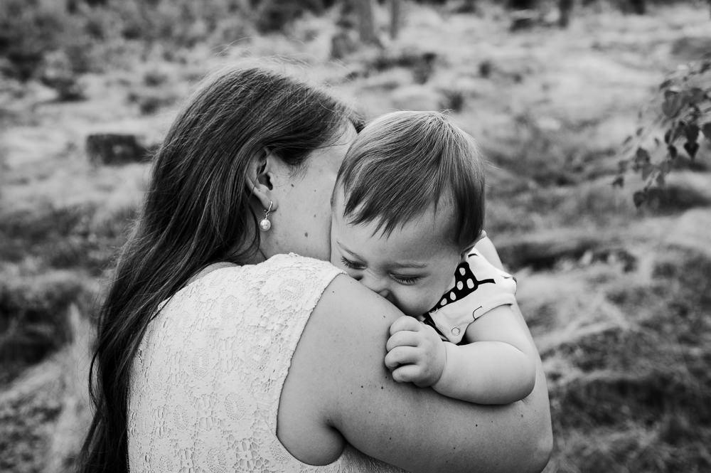 Máma objímá syna při rodinném focení v lese.