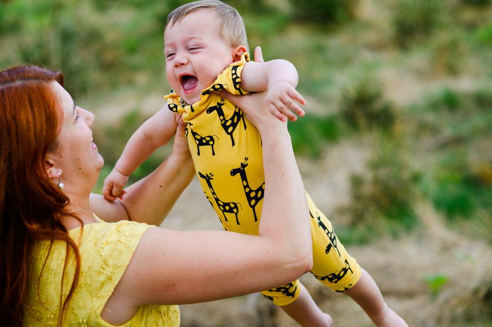 Máma dělá letadlo se synem oblečeným ve žlutém kombíku s žirafy.
