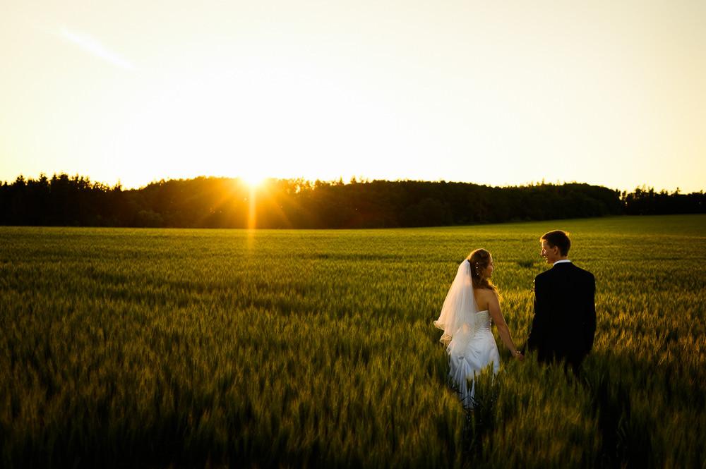Ženich s nevěstou se drží za ruce a jdou obilným polem při západu slunce.