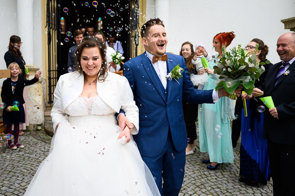 Nevěsta s ženichem s nadšením vychází z kostele, zatímco na ně svatebčané hází rýži.